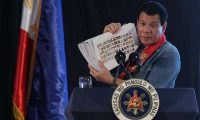 'Duterte has been accused of rabble-rousing populism, having inflated drug use statistics in his speeches.' Philippine president Rodrigo Duterte holds a compilation of pictures of people involved in drugs. Photograph: Lean Daval Jr/Reuters