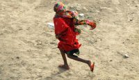 A girl runs to get a cooked meal at a camp for Somalis displaced by famine in 2011 in Mogadishu. Photo: Getty Images.