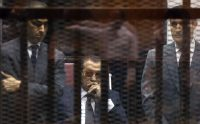 The ousted Egyptian president Hosni Mubarak in the defendant's cage in a Cairo courtroom in between his sons, Gamal and Alaa, in 2015.