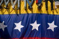 Un grupo de venezolanos se sienta sobre una bandera para protestar contra el presidente Nicolás Maduro en Caracas, Venezuela. Credit Alejandro Cegarra/Associated Press