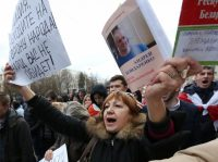 """A protester shouts slogans and holds a poster reading """"Police, come to the side of people! People will not hurt you!"""" during an opposition protest on March 15 in Minsk, Belarus. About 3,000 people took part in the protest, local media reported. (Tatyana Zenkovich/European Pressphoto Agency)"""