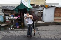A couple embrace in a squatters village in Mexico City on June 25, 2012. Residents of the neighborhood were living without running water and with little electricity and were subject to frequent flooding from rainstorms. (John Moore/Getty Images)
