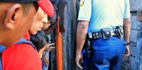 Residents look on as a police investigator inspects the body of a suspected drug pusher, along an alley in Quezon city. Romeo Ranoco/Reuters