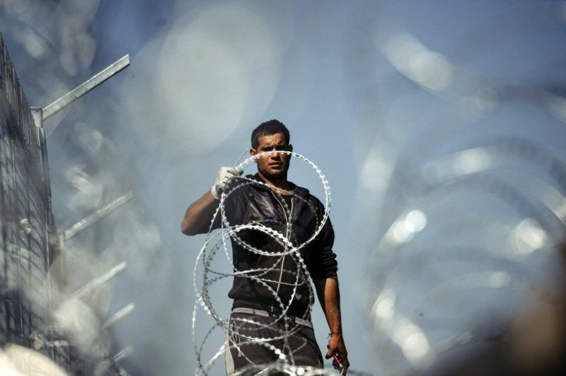 A worker attaches barbed wire to a border fence to prevent illegal crossings by migrants at the Bulgarian-Turkish border in March 2016. (Dimitar Dilkoff/Agence France-Presse via Getty Images)