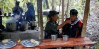 Yuli and Eduar of the 51st Front of the Revolutionary Armed Forces of Colombia (FARC) eat at a camp in Cordillera Oriental, Colombia, August 16, 2016. Picture taken August 16, 2016. REUTERS/John Vizcaino - RTX2N6TF