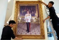 Thai workers installing a framed photograph of King Maha Vajiralongkorn at a shopping mall last December in Bangkok. Credit Rungroj Yongrit/European Pressphoto Agency