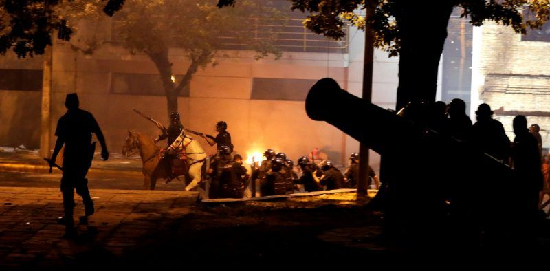 Police on horseback ride past a statue of a cannon during a protest against a possible change in law to allow for presidential re-election in front of the Congress building in Asuncion, Paraguay, March 31, 2017. REUTERS/Jorge Adorno - RTX33LCU