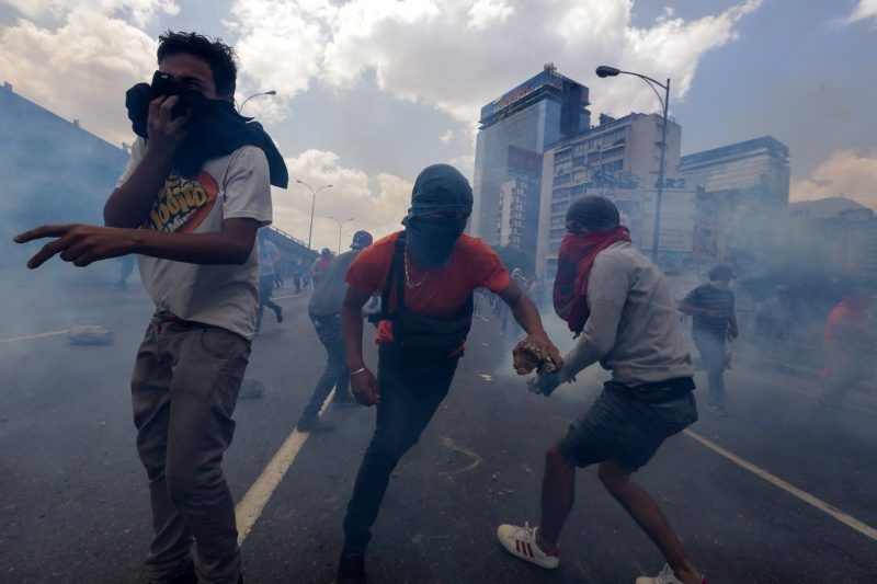 Manifestantes en medio de un ataque con gas lacrimógeno durante una protesta contra el gobierno en Caracas, el jueves 6 de abril. Credit Cristian Hernandez/EPA