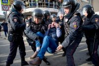Riot police officers detain a protester during an anti-corruption rally in central Moscow on Sunday. (Alexander Utkin/Agence France-Presse via Getty Images)