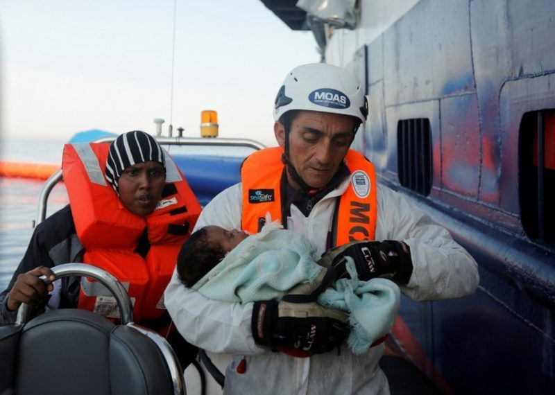 A rescuer of the Malta-based Migrant Offshore Aid Station carries a migrant baby rescued from a wooden boat in the Mediterranean Sea off the coast of Sabratha in Libya this month. (Darrin Zammit Lupi/Reuters)