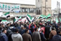Syrians chant slogans and wave pre-Baath Syrian flags during a gathering on the sixth anniversary of the conflict in their country, in the village of Maarat al-Numan, on March 17, 2017. (Mohamed al-Bakour/AFP via Getty Images)