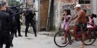 Residents react as policemen take position during an operation in the Mare slums complex in Rio de Janeiro March 26, 2014. Brazil will deploy federal troops to Rio de Janeiro to help quell a surge in violent crime following attacks by drug traffickers on police posts in three slums on the north side of the city, government officials said on Friday. Less than three months before Rio welcomes tens of thousands of foreign soccer fans for the World Cup, the attacks cast new doubts on government efforts to expel gangs from slums using a strong police presence. The city will host the Olympics in 2016. REUTERS/Ricardo Moraes (BRAZIL - Tags: CRIME LAW TPX IMAGES OF THE DAY) - RTR3IPYF