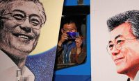 A supporter takes pictures between pictures of the South Korean President-elect Moon Jae-In, as Moon speaks to his supporters after he was declared the winner of the election South Korea, May 10, 2017. Credit Jeon Heon-Kyun/European Pressphoto Agency