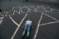 """Una mujer yace en medio de la calle con el grafiti """"Maduro, renuncia ya"""" durante un plantón de la oposición contra el gobierno, el 15 de mayo en Caracas. Credit Fernando Llano/Associated Press"""