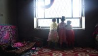 Children of displaced families peer out of the window of a former government building in Ibb, Yemen. Photo: Getty Images.