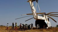 Men unload boxes of nutritional supplements from a helicopter prior to a humanitarian food distribution carried out by the United Nations World Food Programme in Thonyor, Leer county, South Sudan, on 25 February 2017. REUTERS/Siegfried Modola.
