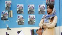 An Iranian woman stands next to a wall plastered with election posters of Iranian President and election candidate Hassan Rouhani on a street in the capital Tehran, on 17 May 2017. AFP/Atta Kenare