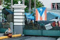 Una estudiante en las puertas de la Universidad de Puerto Rico, campus de Río Piedras, en San Juan, el 11 de mayo de 2017. La universidad ha estado en huelga por dos meses en protesta por una propuesta de recorte presupuestario por casi 500 millones de dólares. Credit Erika P. Rodríguez para The New York Times