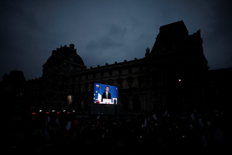 President-elect Emmanuel Macron is seen on a giant screen near the Louvre in Paris on Sunday. Credit Benoit Tessier/Reuters