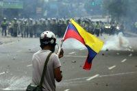 Un manifestante ondea la bandera tricolor de Venezuela frente a las fuerzas de seguridad en una protesta en Caracas, el 24 de mayo de 2017. Credit Mauricio Duenas Castaneda/European Pressphoto Agency