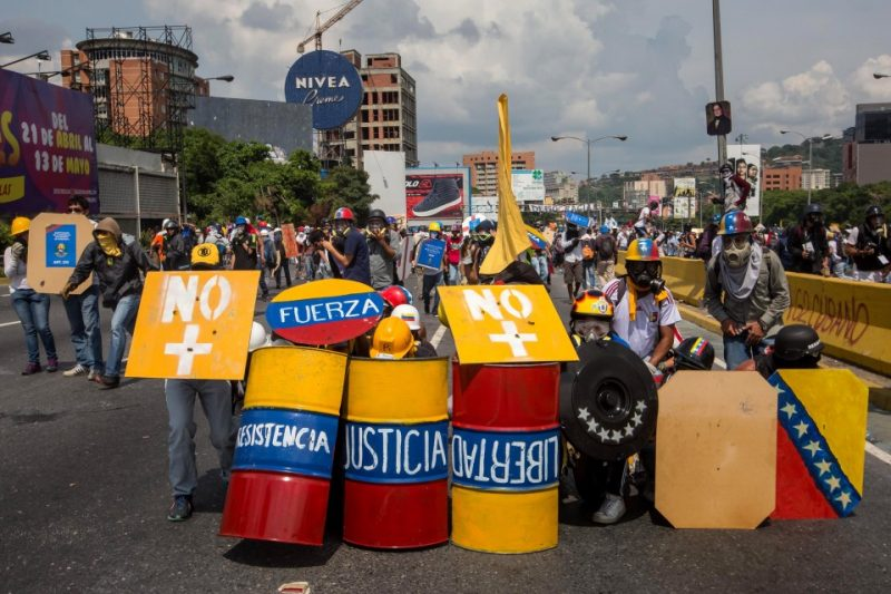 Demonstrators who oppose the Venezuelan government clash with police on a main street of Caracas on Wednesday. The authorities used tear gas and water cannons to disperse protesters who are trying to reach the Supreme Justice Tribunal building. (Miguel Gutierrez/European Pressphoto Agency)