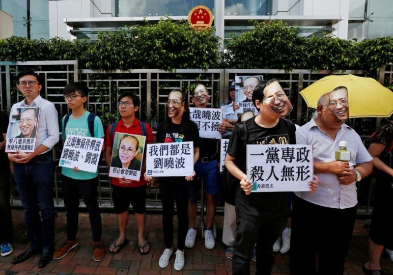 Protesters supporting Chinese Nobel Peace Prize winner Liu Xiaobo stand outside China's Liaison Office in Hong Kong on Tuesday. Some wear masks depicting the human right activist, who was recently released from prison to get treatment for cancer. (Bobby Yip/Reuters)