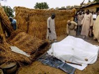 Residents arrange under a white sheet victims of a suicide bombing in Koffa on June 19, 2017. At least 16 people were killed in suicide bomb attacks near a camp for those made homeless by Boko Haram violence in northeast Nigeria, emergency services said on June 19, 2017. (AFP/Getty Images)