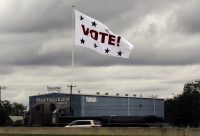 """A huge """"Vote!"""" flag waves above Interstate 35 as motorists pass, in San Antonio, on Nov. 8. (Eric Gay/Associated Press)"""