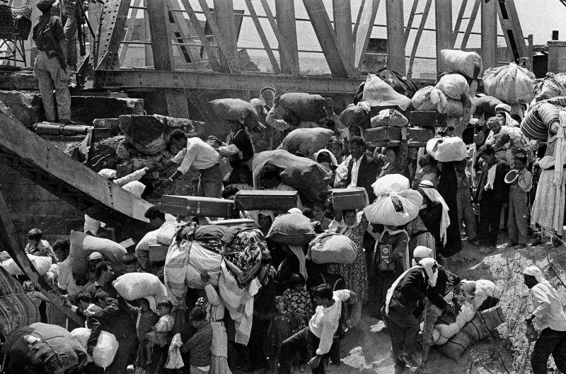 June, 1967, Palestinian refugees carry their belongings as they prepare to cross the wrecked Allenby Bridge over the Jordan River from the Israeli-occupied section of Jordan. Credit Bernard Frye/Associated Press
