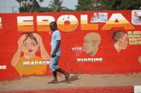 A Liberian man walks past an Ebola awareness painting on a wall in downtown Monrovia, Liberia, in 2015. (Ahmed Jallanzo/European Pressphoto Agency)