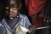 A boy eats out of a ladle at his home in Ngop in South Sudan in March. The Norwegian Refugee Council, a humanitarian group, distributed food for more than 7,100 people in Ngop. (Albert Gonzalez/Agence France-Presse via Getty Images)