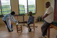 John Brimah, a la derecha, tenía lepra cuando era niño y ahora supervisa el leprosario y el Centro de Rehabilitación de Tuberculosis en Ganta, Liberia. A la izquierda, Bindu Daddah, una enfermera, revisa las lesiones de un paciente llamado John Flomo. Credit Monique Jaques para The New York Times