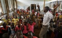 A teacher leads a mixed class of South Sudanese refugee children and Ugandan children in singing during class in a tarpaulin tent on June 7 at the Ombechi Primary School in the Bidi Bidi refugee settlement in northern Uganda. (Ben Curtis/AP)