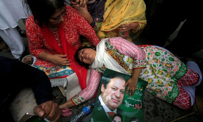 A supporter of Pakistan's Prime Minister Nawaz Sharif passes out in Lahore, Pakistan, after the Supreme Court's decision to disqualify Sharif on Friday. Credit Mohsin Raza/Reuters