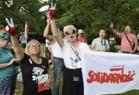 A group of protesters holding a flag with the Solidarity trade union logo shout slogans outside the Senate building during a debate on a bill that gives politicians influence on the nation's top court, in Warsaw, Friday. (Alik Keplicz/AP)