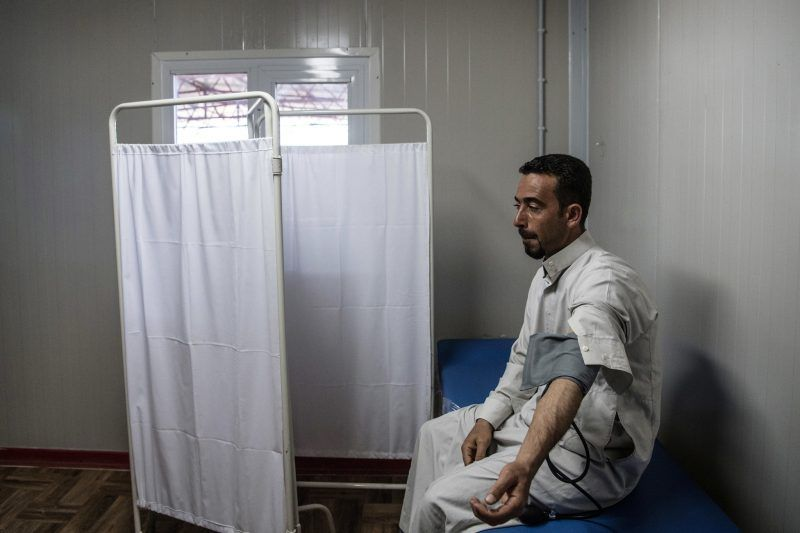Awaiting a doctor in the Hamam al-Alil refugee camp, near Mosul, in April. Credit Carl Court/Getty Images