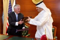 Qatar's foreign minister Sheikh Mohammed bin Abdulrahman al-Thani and Secretary of State Rex Tillerson exchange a memorandum of understanding in Doha, Qatar, on Tuesday. (Naseem Zeitoon/Reuters)