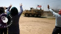 People gesture at a U.S military vehicle travelling in Amuda province, northern Syria, on 29 April 2017. REUTERS/Rodi Said