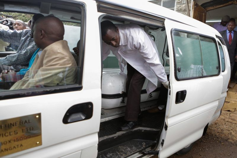 A mortuary attendant closing the door of an ambulance carrying the coffin with the body of Christopher Chege Musando. Credit Daniel Irungu/European Pressphoto Agency