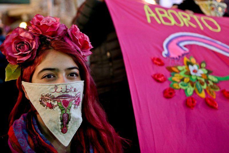 Una mujer que lleva un pañuelo con un útero bordado participa en una marcha a favor de un proyecto de ley respaldado por la presidenta Michelle Bachelet, para legalizar abortos en tres situaciones. Credit Esteban Felix/Associated Press