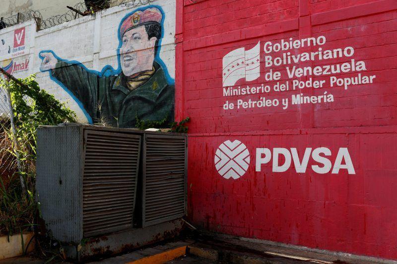 El logo de la petrolera estatal venezolana, PDVSA, aparece junto a un mural del presidente Hugo Chávez, en una estación de gasolina en Caracas, el 2 de marzo de 2017. Carlos Garcia Rawlins/Reuters
