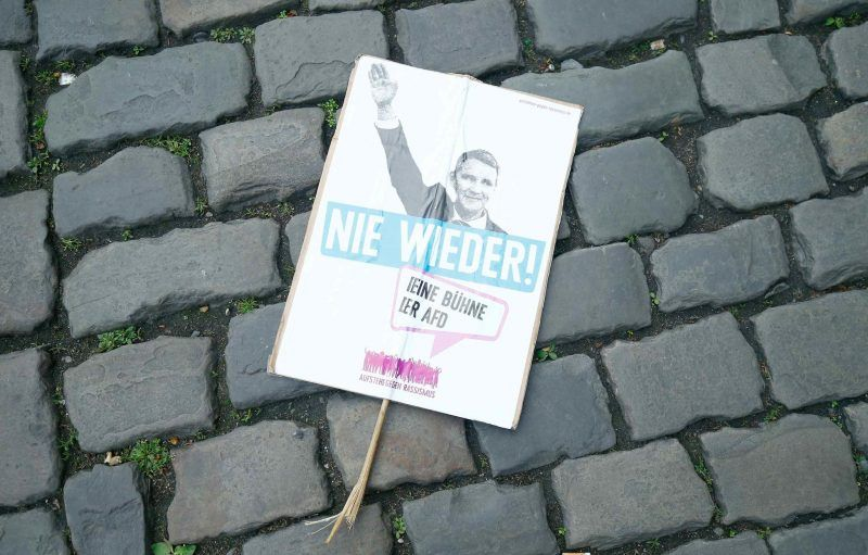 """A sign depicting Bjöern Höecke, a leader of the Alternative for Germany party, with the slogan """"Never again"""" after a protest against the party in Cologne in April. Ralph Orlowski/Reuters"""