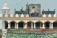 The portrait of Muhammad Ali Jinnah is displayed at the India-Pakistan border in Wagah as a Pakistani Ranger unfurls the flag during a ceremony to celebrate Pakistan's Independence on Monday. Credit Narinder Nanu/Agence France-Presse — Getty Images