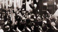 Lenin saluda desde el estribo del vagón en la Estación de Finlandia. Entre el gentío se aprecian los trombones de la banda que tocaba La Marsellesa.