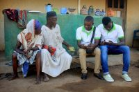 Hayford Amponsam and Bismark Osei (third and fourth from left), two community health workers stationed in Abosamso in rural south-central Ghana, gather basic medical information from a family living in the area. Credit Andrew Green