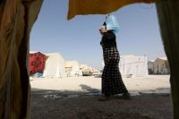 In 2015, a Yazidi woman, who escaped from Islamic State militants, carried water at Sharya refugee camp on the outskirts of Iraq's Dahuk province. (Ari Jala/Reuters)
