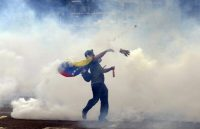A demonstrator throws stones at riot policemen during an anti-government protest in eastern Caracas, Venezuela in 2014. Upheaval in the troubled country could impact regional stability and Colombia's fragile peace, and encourage the global expansion of transnational organized criminal and terrorist networks. (Juan Barreto/AFP/Getty Images)