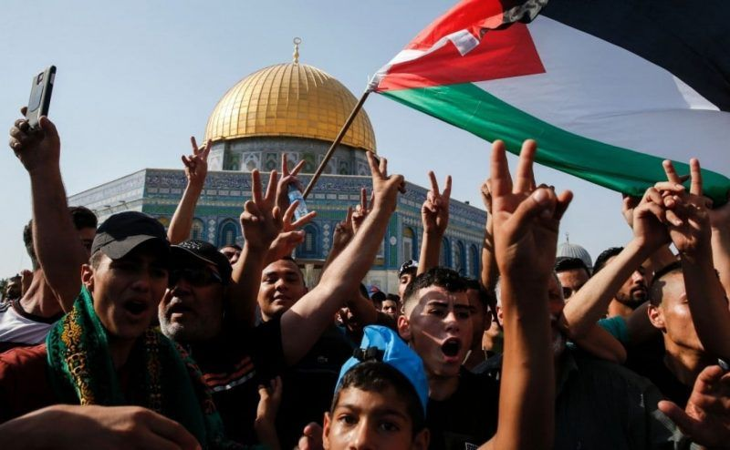Palestinian Muslims wave a national flag and flash the victory gesture in front of the Dome of the Rock in the Haram al-Sharif compound, known to Jews as the Temple Mount, in the Old City of Jerusalem on July 27. (Ahmad Gharabli/Agence France-Presse/Getty Images)