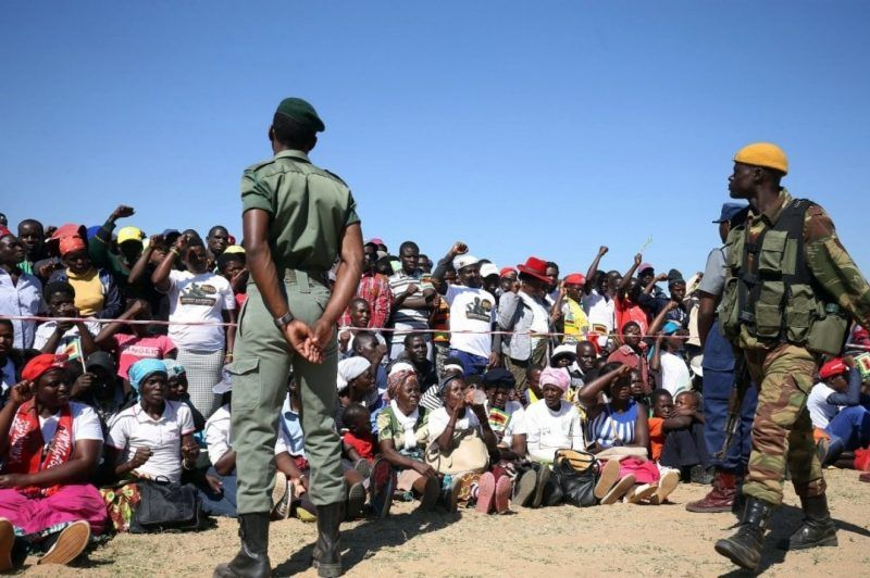 Supporters of Zimbabwean President Robert Mugabe are watched by military personnel as they cheer during a Zimbabwe African National Union (ZANU-PF) party rally in Lupane, Zimbabwe, July 21, 2017. (Aaron Ufumeli/European Pressphoto Agency)