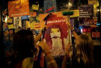 Demonstrators outside the University of Barcelona display a self-designed poster in favor of the banned Oct. 1 independence referendum, on Thursday. Credit Jon Nazca/Reuters
